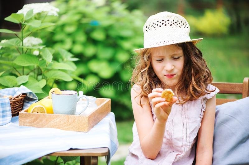 Happy child girl in hat enjoying warm summer day in the blooming garden. Blooming hydrangea flowers on background stock image
