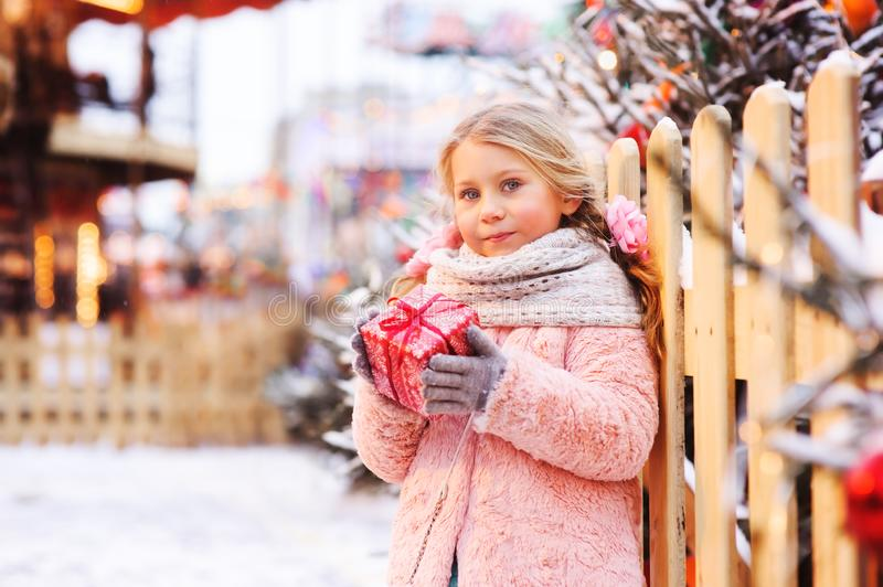Happy child girl holding christmas gift outdoor on the walk in snowy winter city decorated for new year stock images