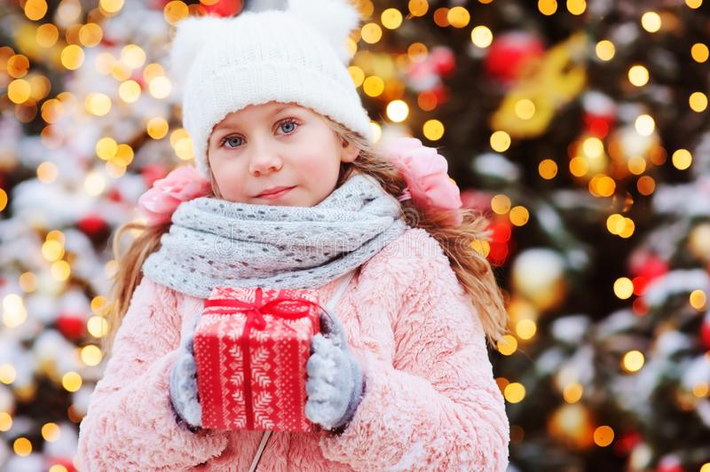 Happy child girl holding christmas gift outdoor on the walk in snowy winter city decorated for new year holidays. Trees with christmas lights on background stock photos