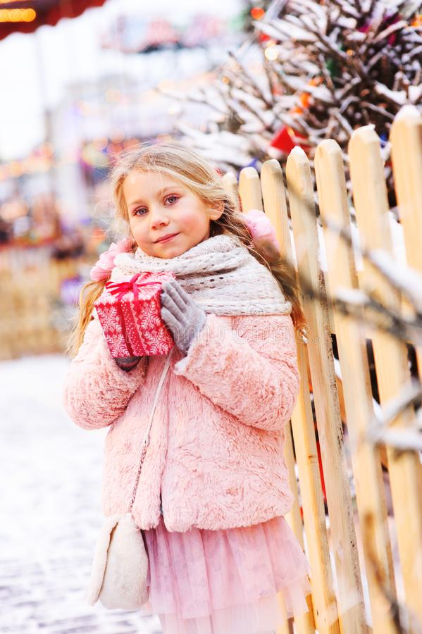 Happy child girl holding christmas gift outdoor on the walk in snowy winter city royalty free stock photo