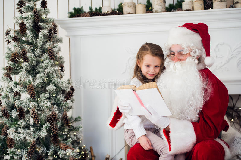 Happy child girl hugging Santa reading book and laughs stock photography