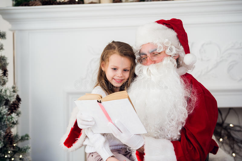 Happy child girl hugging Santa reading book and laughs stock photos