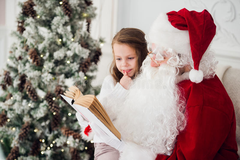 Happy child girl hugging Santa reading book and laughs royalty free stock photos