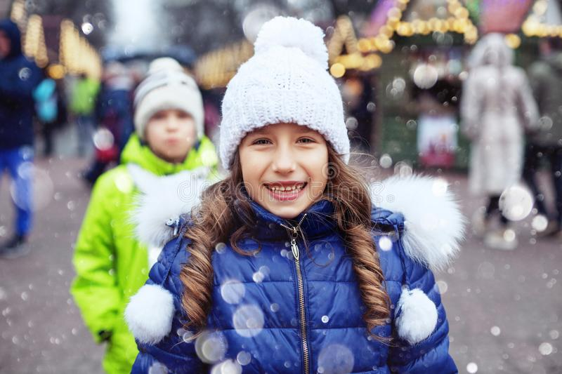 Happy child girl in a jacket and hat walking around the city. The concept of lifestyle, love, Valentine`s Day stock photography
