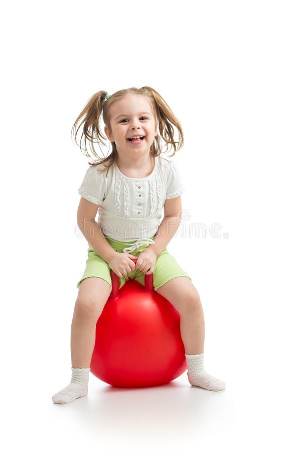 Happy little girl jumping on bouncing ball. Isolated on white. royalty free stock images
