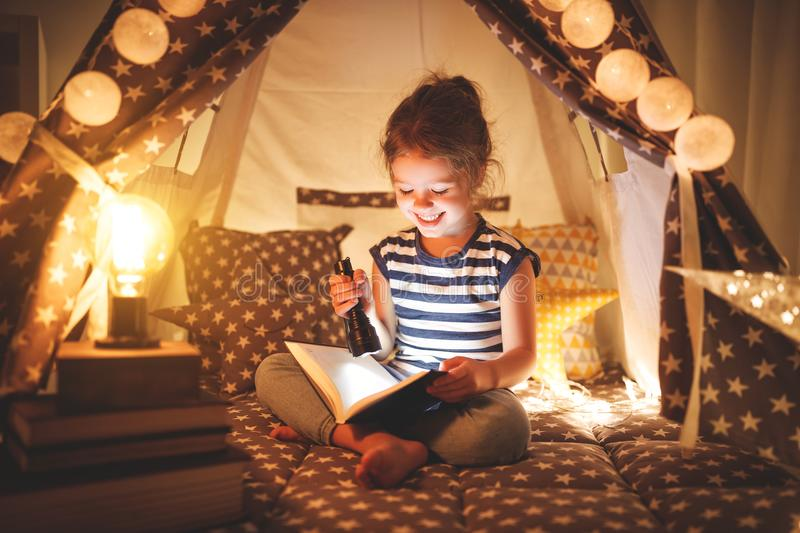Happy child girl laughing and reading book in dark in tent at ho stock photos