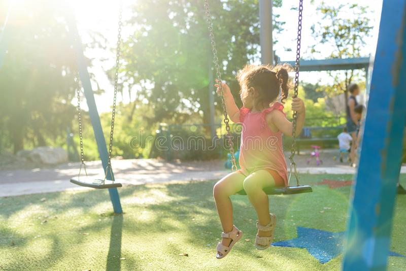 Happy laughing child girl on swing in sunset summer . stock image