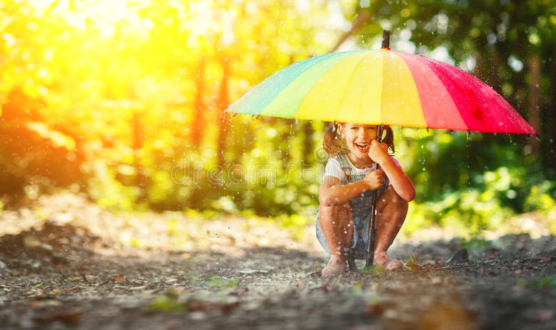 Happy child girl laughs and plays under summer rain with an umbrella stock photography
