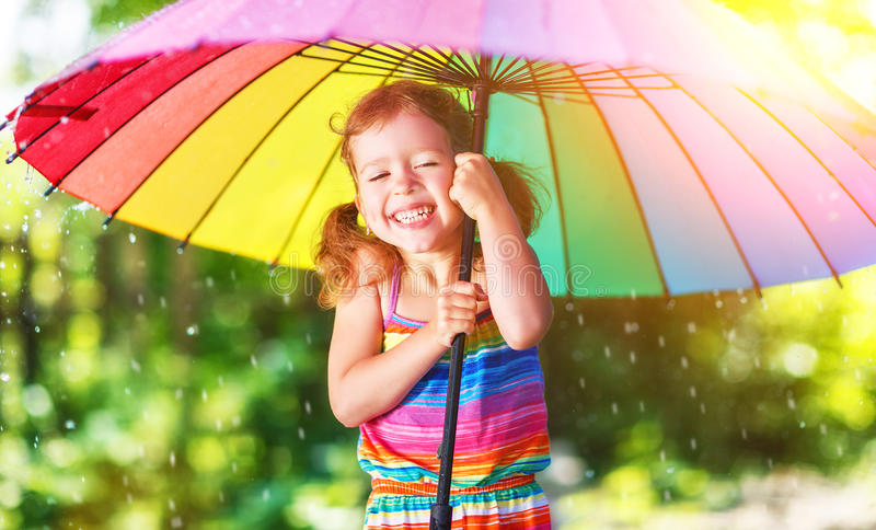 Happy child girl laughs and plays under summer rain with an umbrella. Happy child girl laughs and plays under the summer rain with an umbrella stock image