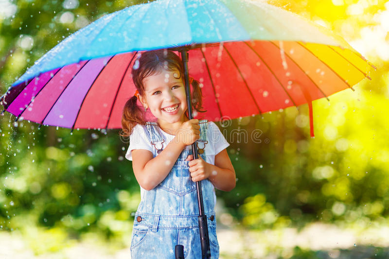 Happy child girl laughs and plays under summer rain with an umbrella. Happy child girl laughs and plays under the summer rain with an umbrella royalty free stock images