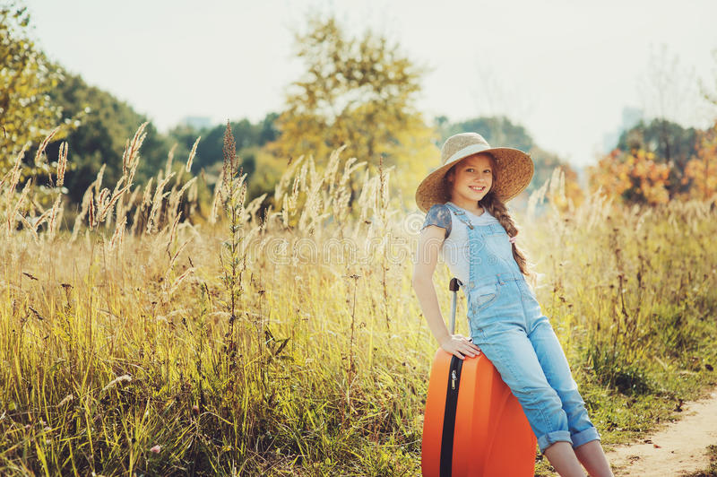 Happy child girl with orange suitcase traveling alone on summer vacation. Kid going to summer camp. royalty free stock images