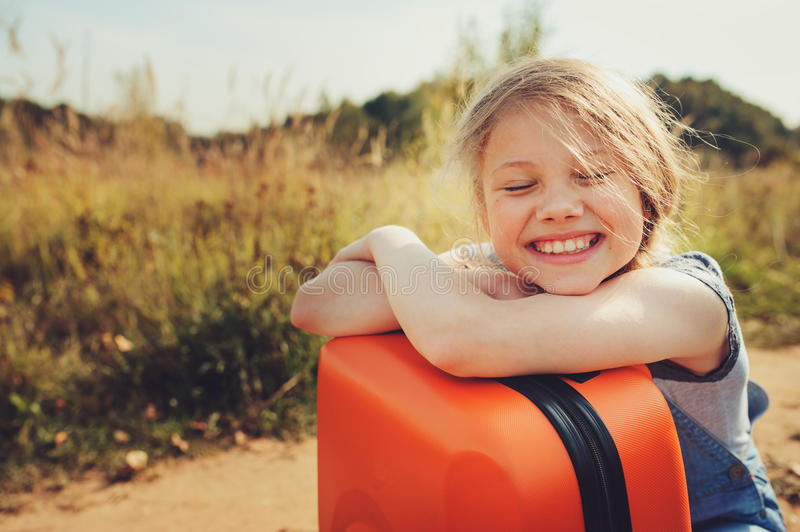 Happy child girl with orange suitcase traveling alone on summer vacation. Kid going to summer camp. Cozy rural scene stock image