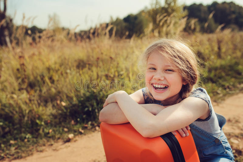 Happy child girl with orange suitcase traveling alone on summer vacation. Kid going to summer camp. royalty free stock photography