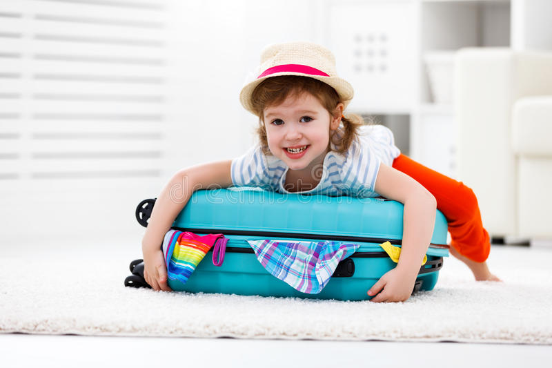 Happy child girl packs clothes into suitcase for travel, vacation. Happy child girl tourist packs clothes into a suitcase for travel, vacation stock images
