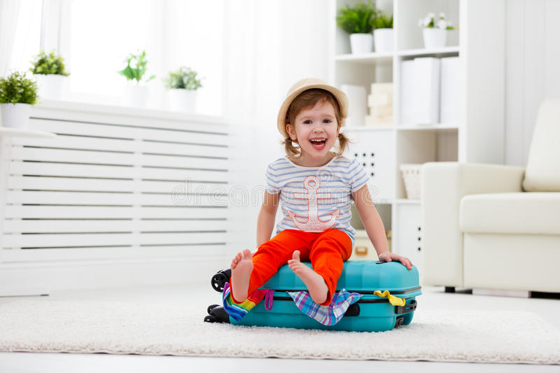 Happy child girl packs clothes into suitcase for travel, vacation. Happy child girl tourist packs clothes into a suitcase for travel, vacation royalty free stock photo