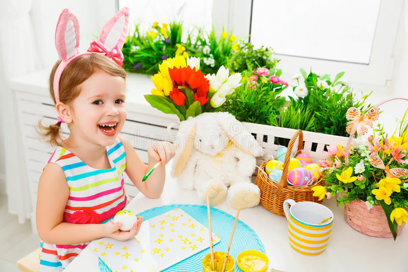 Happy child girl paints eggs for Easter stock images