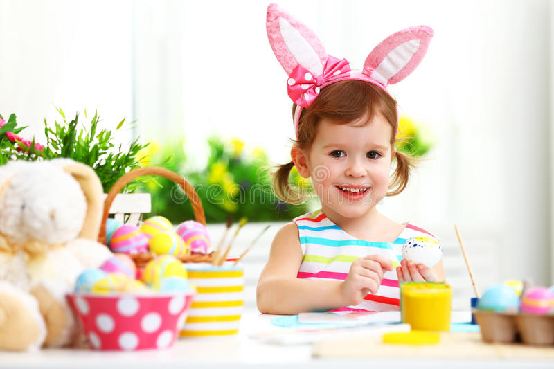 Happy child girl paints eggs for Easter stock image