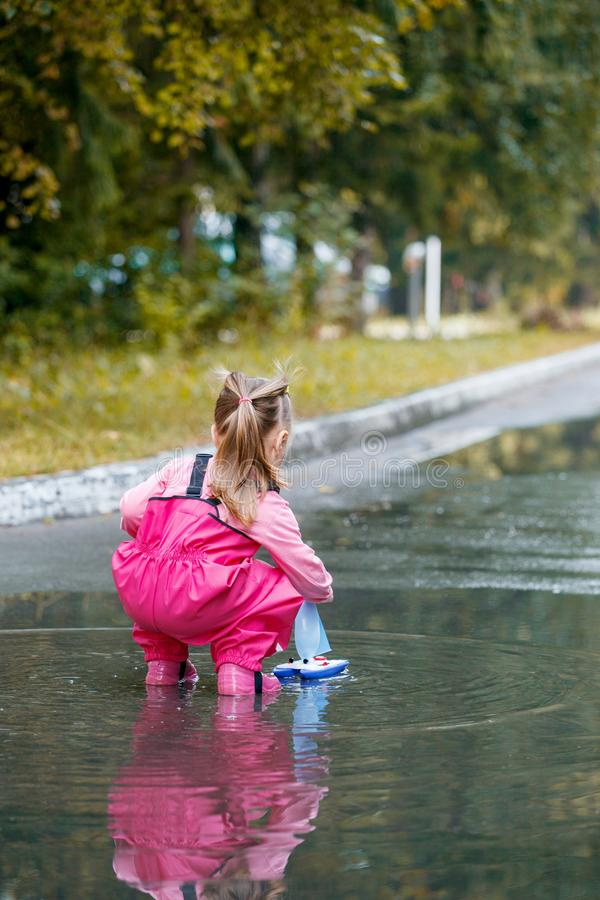 Happy child girl with pink rubber pants and boots in puddle on an autumn walk, seasonal fun childhood game.  royalty free stock image