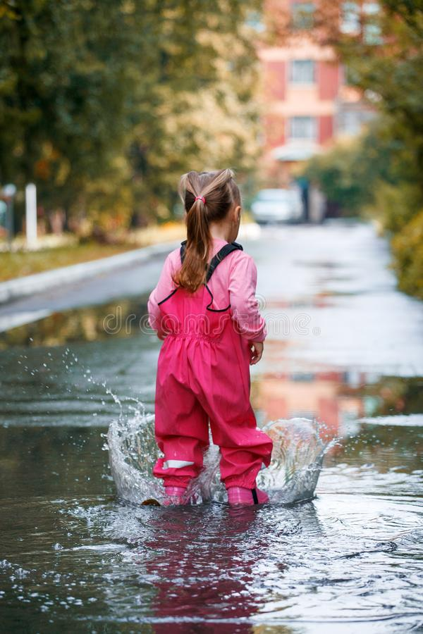 Happy child girl with pink rubber pants and boots in puddle on an autumn walk, seasonal fun childhood game.  stock images