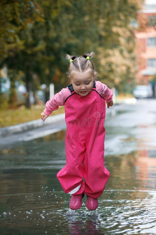 Happy child girl with pink rubber pants and boots in puddle on an autumn walk, seasonal fun childhood game.  royalty free stock photo