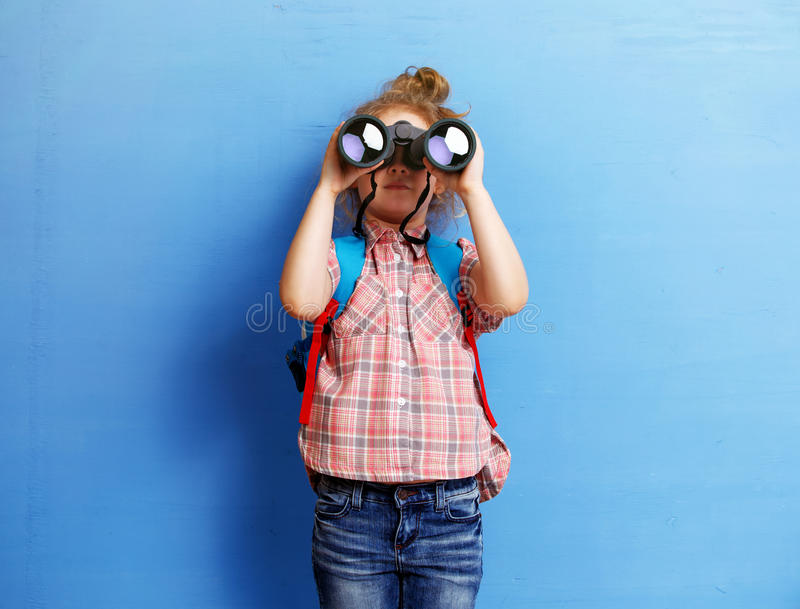 Happy child girl playing with binoculars. explore and adventure concept royalty free stock images