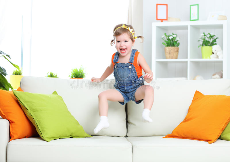 Happy child girl playing and jumping on couch at home stock images