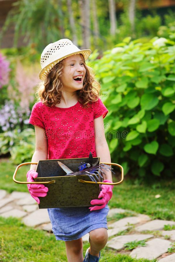 happy child girl playing little gardener and helping in summer garden, wearing hat and gloves, working with tools stock photo
