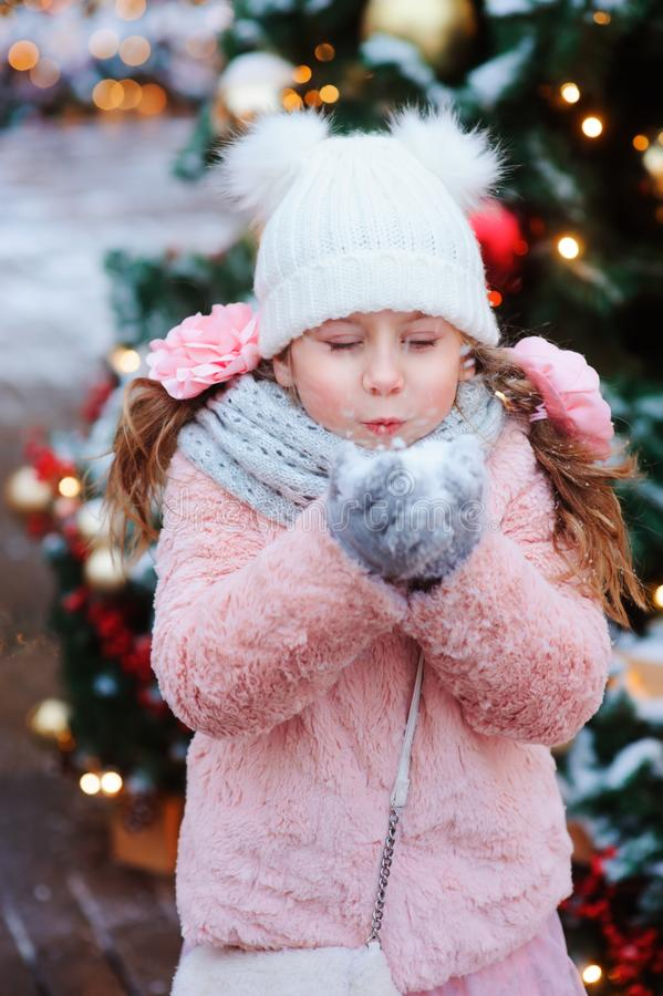 happy child girl playing outdoor on the walk in snowy winter city decorated for new year holidays stock images