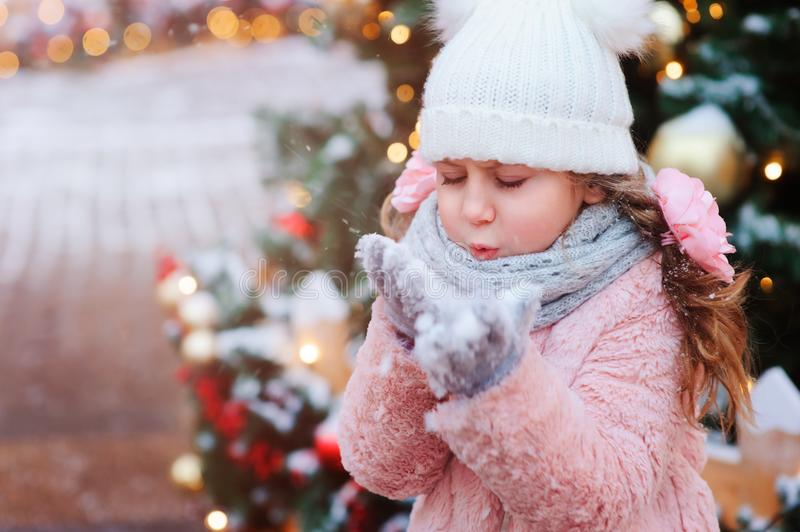 happy child girl playing outdoor on the walk in snowy winter city decorated for new year holidays stock image