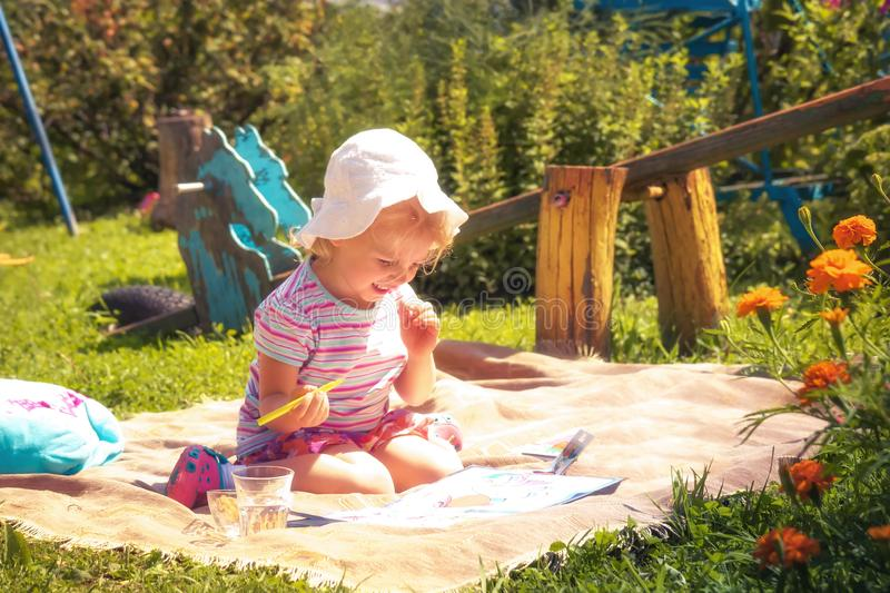 Happy child girl playing outdoors on grass playground in countryside concept childhood lifestyle stock photography