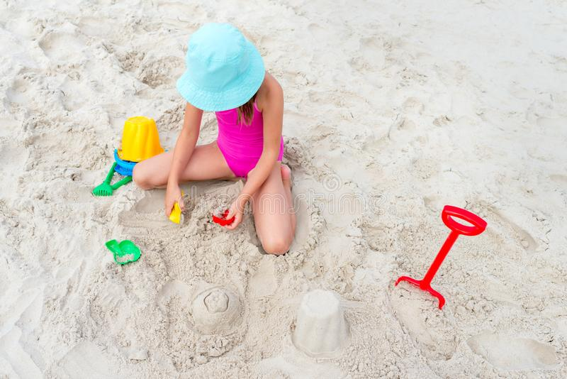 Happy child playing with sand at the beach in summer stock photography