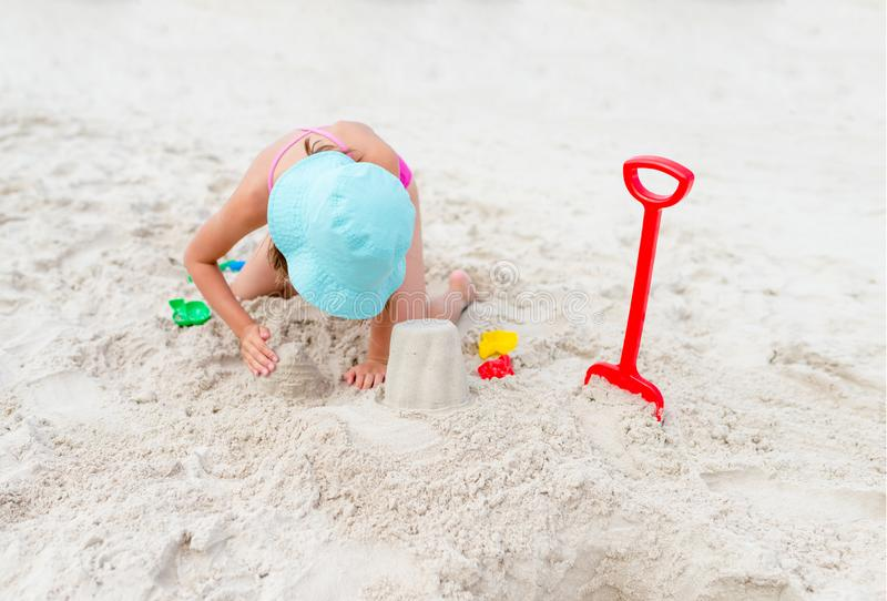 Happy child playing with sand at the beach in summer royalty free stock photography