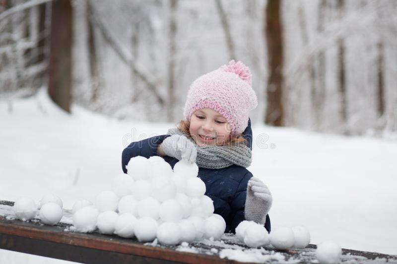 Happy child girl playing with snow on snowy winter walk, making snowballs in the park stock photo