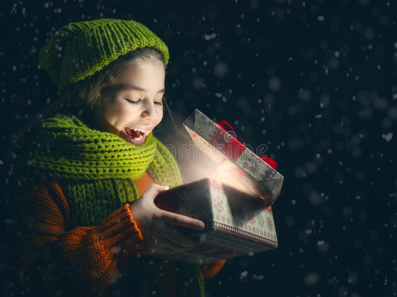 Kid with gift box on dark background royalty free stock photos