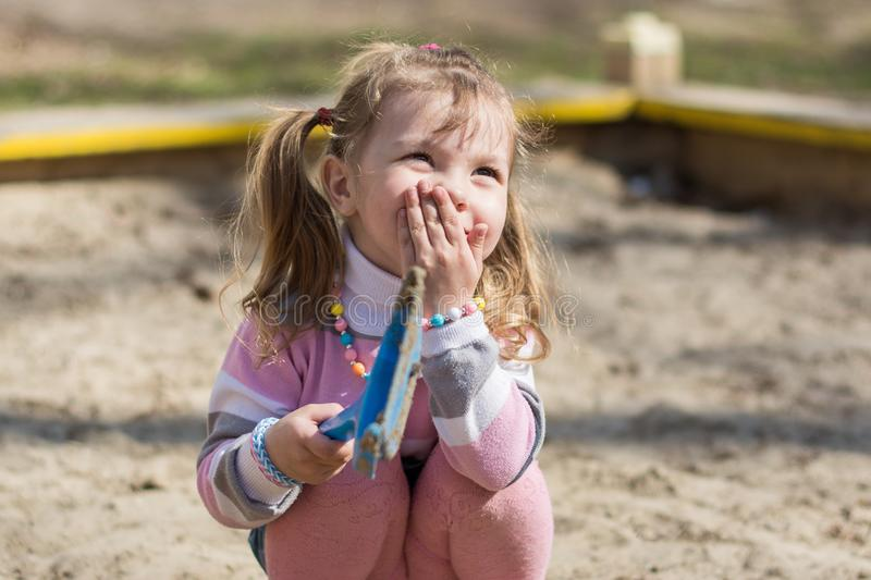 Happy child girl plays with toys in a sandbox, smile, cover your mouth with your hand stock images