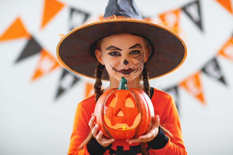 Happy child girl in pumpkin costume to halloween. Happy laughing child girl in pumpkin costume to halloween royalty free stock image
