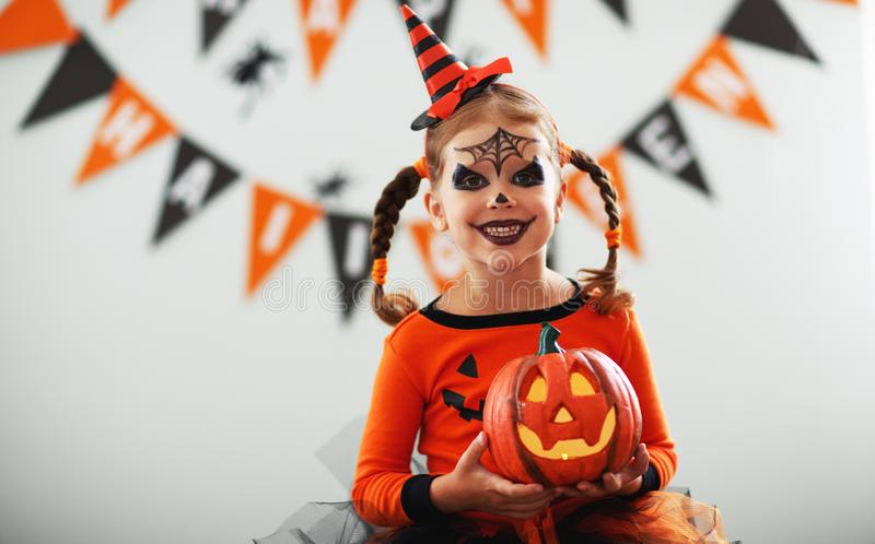 Happy child girl in pumpkin costume to halloween. Happy laughing child girl in pumpkin costume to halloween stock photo