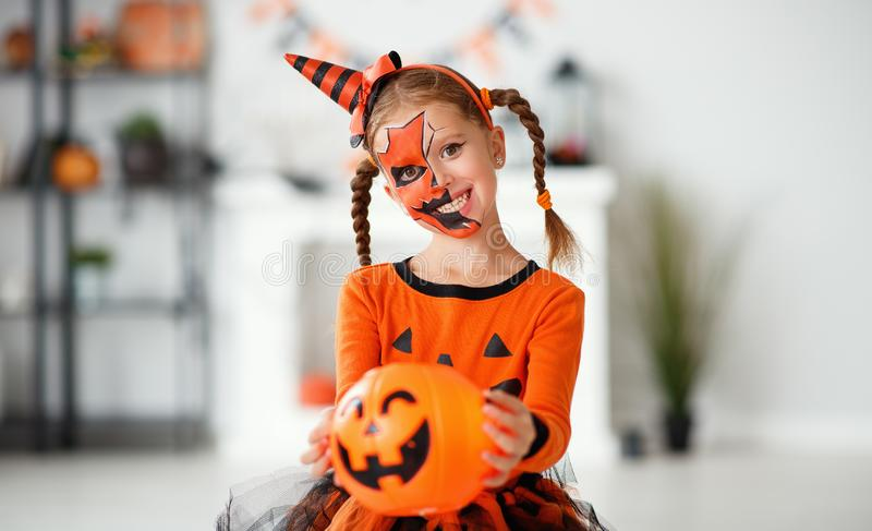 Happy   child girl in pumpkin costume to halloween stock images