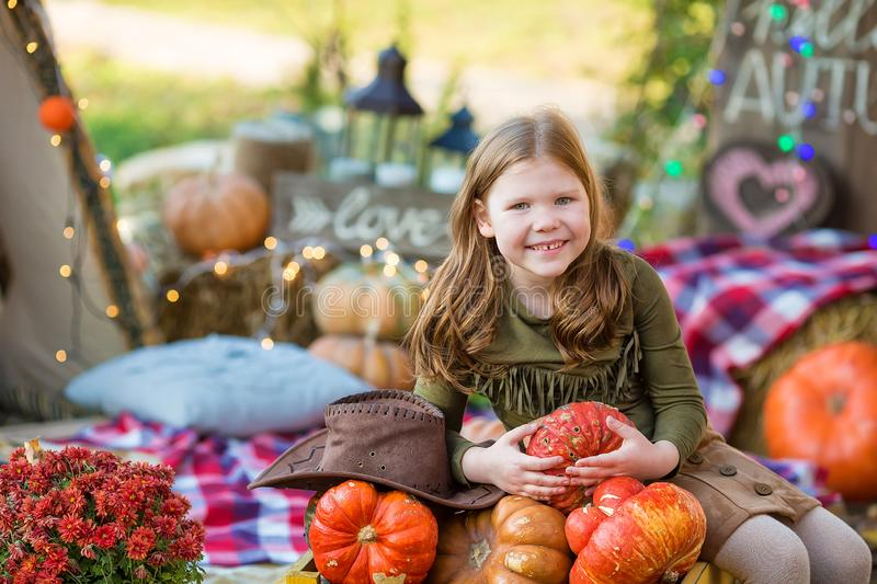 Happy child girl with pumpkin outdoors in halloween park. Happy child girl with pumpkin outdoors in halloween royalty free stock photography