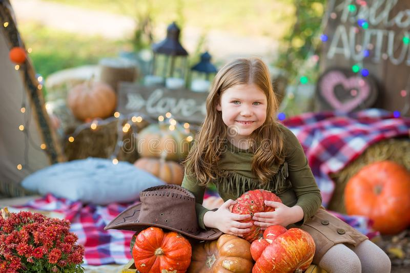 Happy child girl with pumpkin outdoors in halloween park. Happy child girl with pumpkin outdoors in halloween stock images