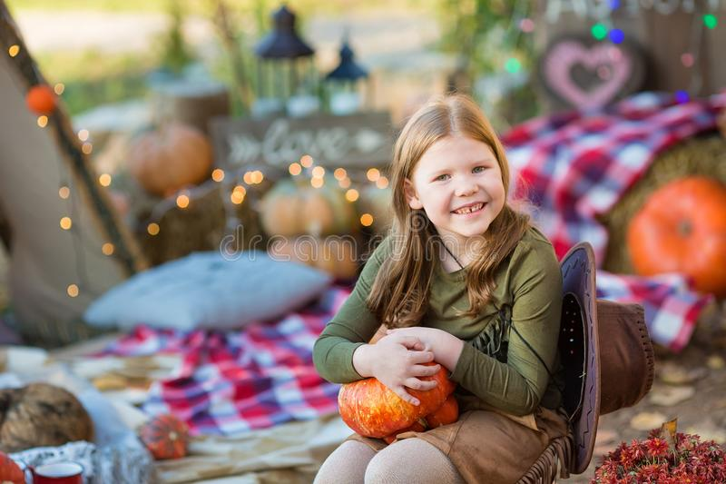 Happy child girl with pumpkin outdoors in halloween park. Happy child girl with pumpkin outdoors in halloween royalty free stock images