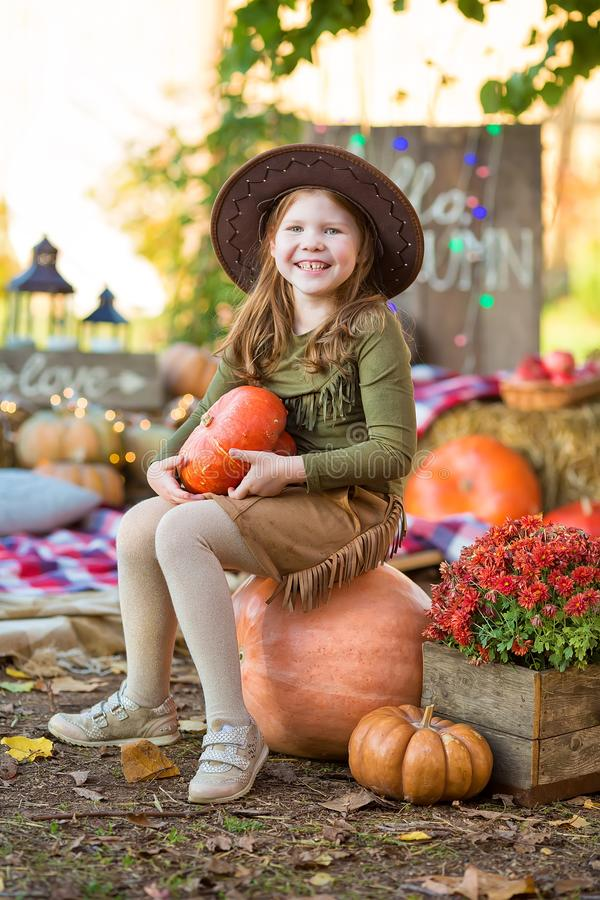 Happy child girl with pumpkin outdoors in halloween park. Happy child girl with pumpkin outdoors in halloween stock photo