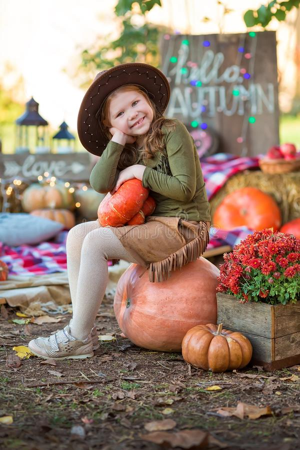 Happy child girl with pumpkin outdoors in halloween park. Happy child girl with pumpkin outdoors in halloween stock photos
