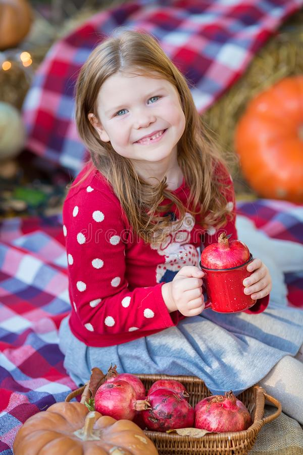 Happy child girl with pumpkin outdoors in halloween park. Happy child girl with pumpkin outdoors in halloween royalty free stock photos