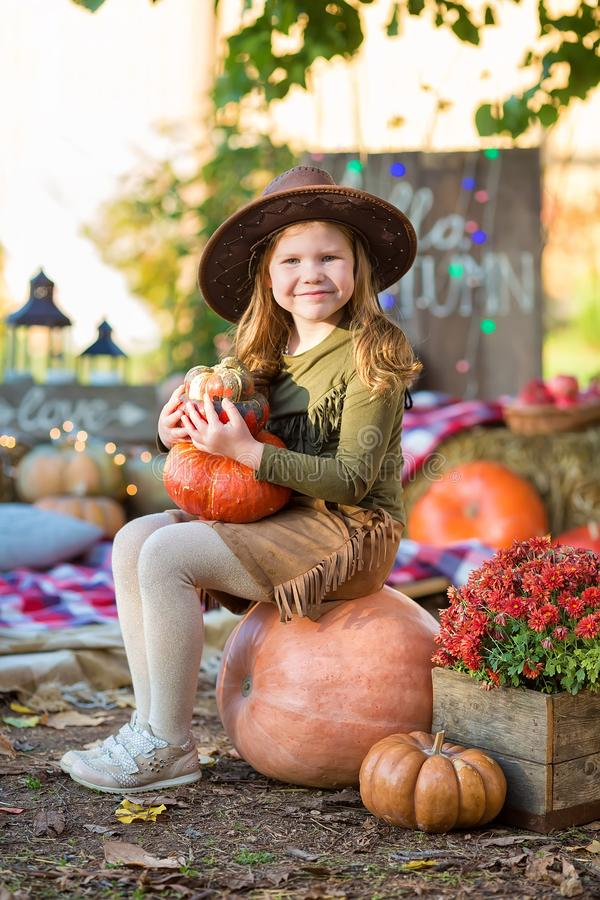 Happy child girl with pumpkin outdoors in halloween park. Happy child girl with pumpkin outdoors in halloween royalty free stock photo