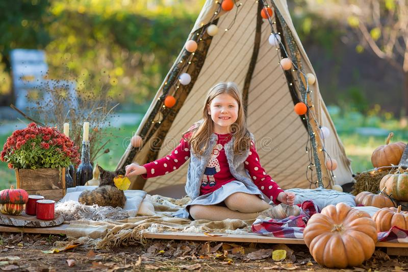 Happy child girl with pumpkin outdoors in halloween park. Happy child girl with pumpkin outdoors in halloween royalty free stock image
