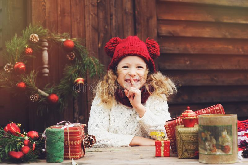 Happy child girl in red hat and scarf wrapping Christmas gifts at cozy country house, decorated for New Year and Christmas stock photography