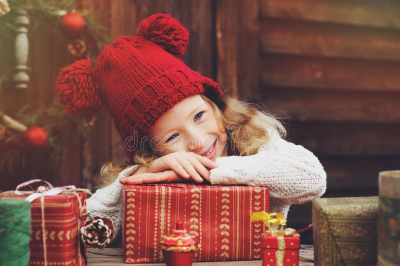 Happy child girl in red hat and scarf wrapping Christmas gifts at cozy country house, decorated for New Year and Christmas. Preparations for holidays with kids royalty free stock image