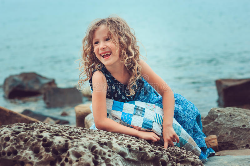 Happy child girl relaxing on the beach, wrapped in cozy blanket royalty free stock image