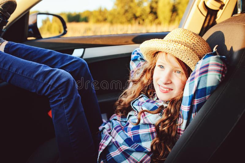 Happy child girl relaxing in car during summer road trip. royalty free stock images